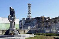 Eine Statue vor dem Kraftwerksgelände (links) und der Sarkophag des zerstörten Blocks 4 (rechts) Bild: de.wikipedia.org