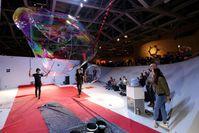 Höchste Konzentration beim Rekordversuch. Die Künstler nutzen Spezialseifenlauge, um eine möglichst große und langlebige Seifenblase zu erzeugen, die sich auch schließen lässt. Quelle: Foto: Matthias Leitzke, phaeno (idw)