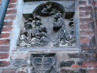Asylzeichen am Frauendom zu München (Kreuz in einem Schild, unten), unter einer Darstellung der Ölbergszene, die außen an Kirchen Hinweis auf ein Kirchenasyl ist.