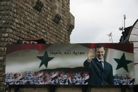 Billboard with portrait of Assad and the text 'God protects Syria' on the old city wall of Damascus 2006