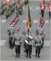 Fallschirmjäger im Großen Dienstanzug mit bordeauxrotem Barett und grüner Waffenfarbe. Vorne die Fahnenabordnung mit Truppenfahnen der Bundeswehr.