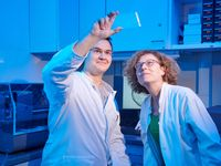 Tobias Claff und Prof. Dr. Christa Müller von der Universität Bonn betrachten einen Glasträger, auf dem sich die Opioid-Rezeptor-Kristalle bilden. Quelle: © Foto: Volker Lannert/Uni Bonn (idw)