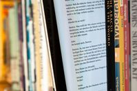 Tablet-Computer zwischen Büchern mit dargestelltem E-Book
