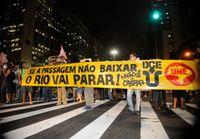 """Demonstranten auf einer Straße von Rio de Janeiro. Auf dem Banner steht """"Se a passagem não baixar, o Rio vai parar!"""", übersetzt: """"Wenn die Fahrkarten (-preise) nicht runtergehen, kommt Rio zum Stehen!"""""""