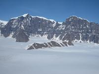 Die Watkins-Berge im südlichen Ostgrönland mit dem höchsten Gipfel Grönlands, Gunbjørn Fjeld (3,7 km über NN) im Hintergrund. Blick von ca. 2 km über Meereshöhe zum 1,5 km hohen Watkins-Steilabbruch, der sich in Basalte einschneidet, die am Übergang vom Paleozän zum Eozän vor 56 Mio. Jahren ausbrachen, damals nahezu auf Meereshöhe.