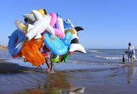 Gummitiere und andere aufblasbare Badespielzeuge eines fliegenden Händlers an einem Badestrand