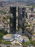 """Zentrale der Deutschen Bank in Frankfurt am Main; im Volksmund werden die beiden Hochhäuser auch als """"Soll und Haben"""" bezeichnet."""