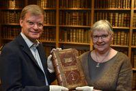 Die Dekanin der Theologischen Fakultät der Universität Jena, Prof. Dr. Corinna Dahlgrün, überreicht den Band an Dr. Joachim Ott von der Thüringer Universitäts- und Landesbibliothek.
