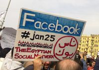 "A man during the 2011 Egyptian protests carrying a card saying ""Facebook,#jan25, The Egyptian Social Network"""