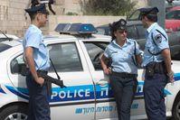 Israelische Polizisten vor einem Streifenwagen