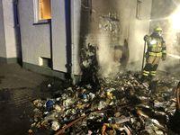 Komplett abgebrannte Mülltonnen, im Hintergrund die beschädigte Hauswand, sowie der beschädigte Rolladen Bild: Polizei