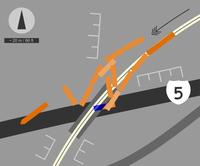 Darstellung der Unfallstelle. Die ziehende Lokomotive liegt ganz links im Bild auf der Richtungsfahrbahn Süd des Interstate 5. Das hinterste der 12 Fahrzeuge – die zweite Lokomotive am Zugschluss – ist (rechts-oben) als einziges Fahrzeug nicht entgleist. Ein Waggon (blau) liegt unter der Brücke. Pfeil = Fahrtrichtung des Zugs. E-Marken = Böschungen