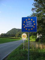 """Eine """"Schengen-Grenze"""" zwischen zwei EU-Staaten, hier beim Übergang von Erl in Tirol (Österreich) nach Nußdorf am Inn in Bayern (Deutschland): Es gibt keine Grenzkontrollen an der Staatsgrenze, nur ein blaues Schild mit einem Sternenkranz um den Namen des EU-Staates"""