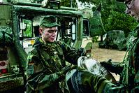 IT-Soldat bei einer Geländeübung an einem geschützen Gefechtsfahrzeug