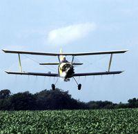 Flugzeug, welches Insektizide über einem Feld versprüht. Diese Form der Pflanzenschutzmittelapplikation ist in der EU verboten