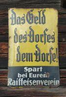 Werbeschild für Raiffeisen an einem Haus in Bad Füssing (Symbolbild)