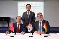 Generalkonsul Wang Shunqing (stehend) bei der Vertragsunterzeichnung von BSU-Direktor Cao Weidong und Axel Hellmann. Bild: Eintracht Frankfurt