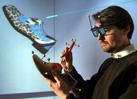 Schuhe in der 3D-Welt: Prof. Dr. Guido Brunnett hält eine Schuhattrappe in der Hand, deren Sensoren Bewegungen auf das virtuelle Schuhmodell übertragen. Farben, Materialien, Absätze oder Schmuckelemente können mit einem Auswahlstift festgelegt werden. Foto: TU Chemnitz