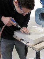 """Steinmetz bei der Arbeit - Absaugvorrichtungen nehmen den Staub gleich an der Quelle auf. Bild: """"obs/Berufsgenossenschaft der Bauwirtschaft"""""""
