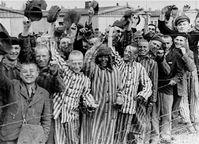 Häftlinge, teilweise in gestreifter KZ-Häftlingskleidung, nach der Befreiung des Konzentrationslagers Dachau. Aufnahme vom 29. April 1945.