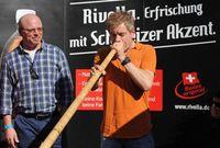 Michael Mittermeier und Finalist Rainer Bothe beim Selbstversuch auf dem Finale des Rivella-Alphornlautblaswettbewerbs. Bild: Andreas Gebert/obs/Rivella AG