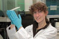 """Dr. Christa Hohoff mit einem Probenträger und einem wichtigen """"Mitarbeiter"""" - dem Pipettierroboter, der für die molekularbiologische Untersuchung genutzt wurde Foto: WWU - tw"""