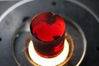 Frisch aus der Schmelze erstarrte Zinkoxid-Kristalle schimmern rot, weil sie noch atomare Defekte enthalten. Ein nachfolgendes Tempern - Erhitzen auf ca. 1000°C - bringt die Defekte zum Verschwinden und liefert ein blassgelbes Material, das zu Halbleiter-Wafern verarbeitet wird. Foto: IKZ