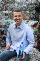 """Dr. Sebastian Stricker mit der neuen """"share""""-Recyclatflasche vor dem Grundstoff seiner Innovation: Plastikmüll. Bild: """"obs/REWE Markt GmbH/share"""""""