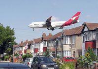 Eine Qantas Boeing 747–400 passiert knapp die Häuser in der Nähe des London Heathrow Airport.