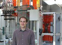 Dr. Hauke Marquardt, Leiter der neuen Emmy Noether-Nachwuchsgruppe im Bayerischen Geoinstitut (BGI), vor dem Hydrauliksystem einer Hochdruckpresse (rechts im Bild).