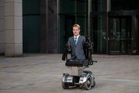 Janis McDavid im Rollstuhl vor dem Bürogebäude
