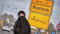 Islamisierung: Ortstafel der Hansestadt Rostock auf Arabisch.