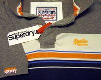 Verschiedene Varianten der Logos und Schriftzüge von Superdry auf einem Poloshirt.