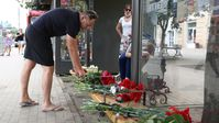 Ein Mann legt am 13. August 2021 am Ort der Tragödie in Woronesch Blumen nieder, um der Todesopfer zu gedenken.